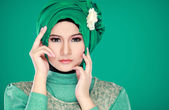 Fashion portrait of young beautiful muslim woman with green cost — Stock Photo