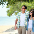 Happy couple walking by beach together in love holding around each other — Stock Photo #37791557