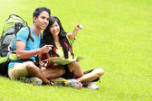 Jeune couple touristique lire la carte et montrer la direction — Photo