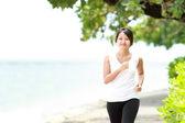 Beautiful girl jogging on the beach — Stock Photo