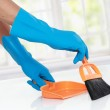 Hand with glove using cleaning broom to clean up — Stock Photo #38499213
