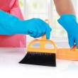 Hand with glove using cleaning broom to clean up — Stock Photo #38499219