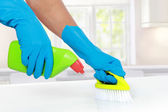 Hand with glove using cleaning brush to clean up — Stock Photo