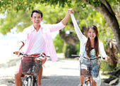 Young couple riding bicycle together — Foto de Stock
