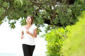 Vacker flicka jogga på stranden — Stockfoto