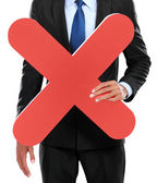 Portrait of businessman holding red cross sign — Stock Photo