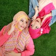 Close up two beautiful happy muslim woman lying on grass — Stock Photo #41021707
