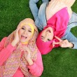 Close up two beautiful happy muslim woman lying on grass — Stock Photo #41021777