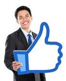 Portrait of businessman holding like sign — Stock Photo