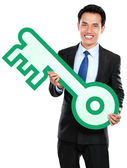 Businessman holding keys symbol — Stock Photo