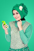 Woman with head scarf holding mobile phone — Stock Photo