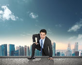 Businessman climbing to the top of the building — Stock Photo