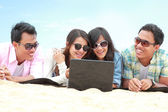 Group Friends Enjoying Beach Holiday together with laptop — Stock Photo