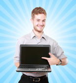 Handsome businessman presenting using laptop with blank screen — Stock Photo