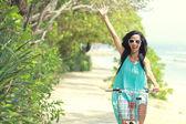 Woman having fun riding bicycle at the beach — Stockfoto