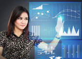 Businesswoman pointing to a graph on transparent touchscreen — Stock Photo