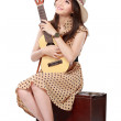 Woman sitting on her suitcase while playing guitar — Stock Photo #49106869