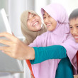 Three muslim kids playing tablet computer — Stock Photo #49999417