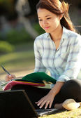 Girl sitting with laptop and books — Stock Photo