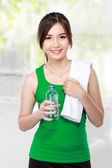 Smiling fitness woman drinking water — Stock Photo
