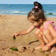 Little girl playing on seaside — Stock Photo #17834445
