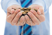 Businessman holding sand and coin — Stock Photo