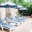 Stock Photo: Beach chairs and umbrellas beside swiming pool