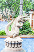 Crocodile statue spray water decorated blue pool — Stock Photo
