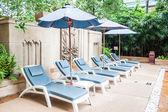 在酒店的游泳池的遮阳伞和沙滩椅 — 图库照片