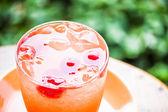Cam, buzlu mix meyve suyu kola yeşil zemin üzerine — Stok fotoğraf