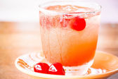 Glass of cold mix fruits juice soda on wood table — Stock Photo