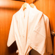 White robes with wooden hangers in hotel wardrobe — Stock Photo