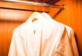 Bathrobes hanging on wooden hangers in wardrobe — Stock Photo