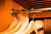 Empty wooden hanger hanging in a wood wardrobe — Stock Photo