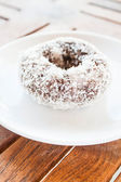 Piece of chocolate coconut donut on white plate — Stock Photo