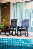 Wooden arm chairs beside the pool — Stock Photo
