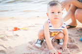 Little cute boy playing sand on the beach — Stock Photo
