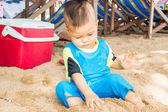 Asian boy playing sand on the beach — Zdjęcie stockowe