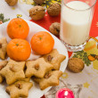 Santa's Cookies with galss of milk nuts candle and oranges - Foto Stock