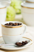 Cup of coffee full of beans — Stock Photo
