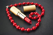 Lipstick and heart shape jewelry — Stock Photo