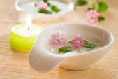 Little flowers in bowl and candle — Foto Stock