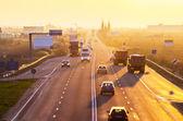 Cars and trucks at sunrise — Stock Photo