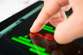 Touching screen of tablet pc with market graph — Stock Photo