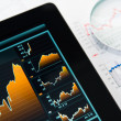 Touching screen of tablet pc with market graph — Stock Photo #13443425