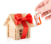 Hand with keys and wooden house — Stock Photo