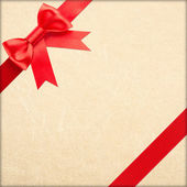 Wrapped vintage gift with red bow — Stock Photo