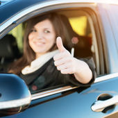 Pretty young woman with thumbs up in her new car — Stock Photo