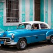 Stock Photo: Blue old car in front of blue house, Cuba