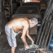 Elderly metalworker in his garage — Stock Photo